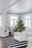 Weiße Holztruhe als Couchtisch und Weihnachtsbaum im Wohnzimmer