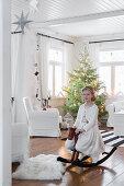 Mädchen mit Schaukelpferd im Wohnzimmer, im Hintergrund Weihnachtsbaum