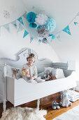 Mädchen mit Puppe auf Holzbett im Kinderzimmer