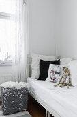 Bett mit Kissen und Nachttisch mit Häkelbezug