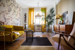 Mustard-yellow sofa, sideboard, table and chairs below window and potted palm in living room
