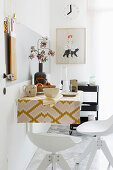 Wall-mounted table with retro tablecloth and bar stools in kitchen
