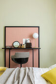 Dressing table against pink panel on green wall in bedroom
