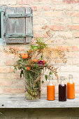 Autumnal bouquet and three bottles of juice against outside wall of house