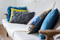 Colourful cushions with various textures on sofa