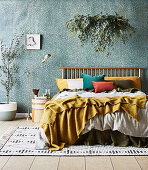 Double bed with pillows, houseplant above, bedside table, standard lamp and olive trees in the bedroom with jade green wallpaper