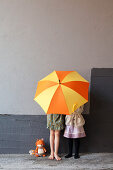 Two girls hiding behind yellow and orange umbrella