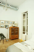 Cabinet with open-fronted compartments below gallery of pictures in bedroom