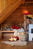 Arrangement of candles and bench next to wood-burning stove in rustic wooden hut