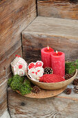 Crocheted Christmas decorations and red candles on rustic wooden steps