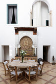 Round table with stone top and chairs in lobby of the Hotel Ryad Dyor (Marrakesh, Morocco)