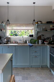 Blue base cabinets and vintage pendant lamps in kitchen