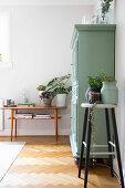 Barhocker und Konsolentisch mit Pflanzen neben grünem Schrank