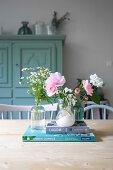 Frische Gartenblumen in drei Väschen und Bücher auf dem Tisch