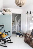 Rocking chair, dolls' pram and grey wardrobe in white nursery