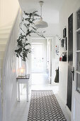 Console table and runner in hallway with white wooden floor