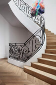 Wooden stairs and curved, wrought-iron banisters in the stairwell