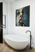 Freestanding bathtub with stand mixer and modern art on the wall in the bathroom