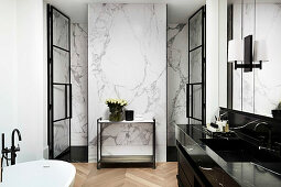 Black marble vanity in luxurious bathroom, wall covered with white marble