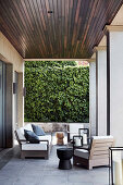 Sofa, armchair and tree trunk stool on covered terrace