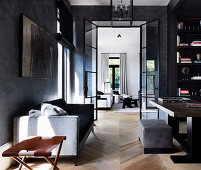 Desk, shelf and sofa in elegant study with dark walls