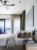 Double bed with pillow collection in the bedroom with balcony