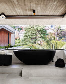 Dark, free-standing bathtub in the bathroom with concrete ceiling, concrete floor and garden view