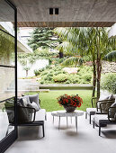 Designer outdoor furniture on a terrace with a concrete ceiling