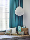 Bench with cushions and hanging lamp in front of window with blue curtain