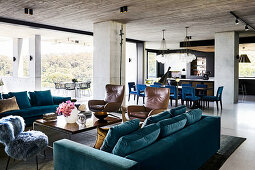 Various seating furniture around coffee table, in the background dining area in open living room with exposed concrete ceiling