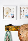 Sea shells and holiday photos in deep frames above coat pegs