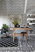 Rustic wooden table and black stools in black-and-white kitchen with various patterns