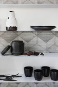 Crockery and cutlery on wall-mounted shelves on monochrome patterned wallpaper