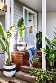 Veranda mit Holztreppe, umgeben von Grünpflanzen, Frau mit Einkaufstüte