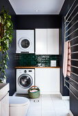 Waschraum mit Waschmaschine und Trockner an Fliesenwand