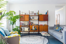 Retro shelving, grey couch and armchair in living room
