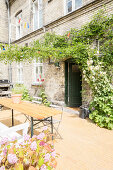 Garden table and climbing plants in sunny courtyard
