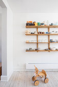 Ride-on toy below crockery on wooden wall-mounted shelving