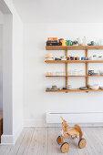 Ride-on toy below crockery on wooden wall-mounted shelving