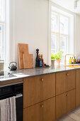 Küchenzeile mit Holzfronten unter den Altbaufenstern