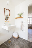 Mirror with organic curved shaped above square sink in bathroom