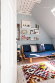 Sofa in teenager's attic bedroom with sloping ceiling