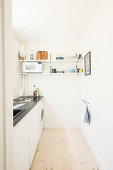 Small, narrow, white kitchen with black worksurface