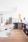 Offener Wohnraum auf der Galerie mit Kamin und Kuhfellteppich