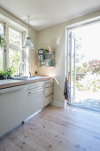 Pale wooden flooring in light-flooded kitchen with garden access