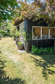 Häuschen mit großen Fenstern im sommerlichen Garten