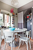 Round table, wooden chairs and fridge with chalkboard paint in niche in kitchen