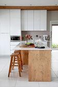 Elegante weiße Küche mit Kücheninsel und Barhockern aus Holz