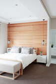 Double bed with bedside cabinets and pendant lamps against wood-panelled wall in elegant bedroom