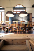 Long dining table and chairs below pendant lamps in converted loft